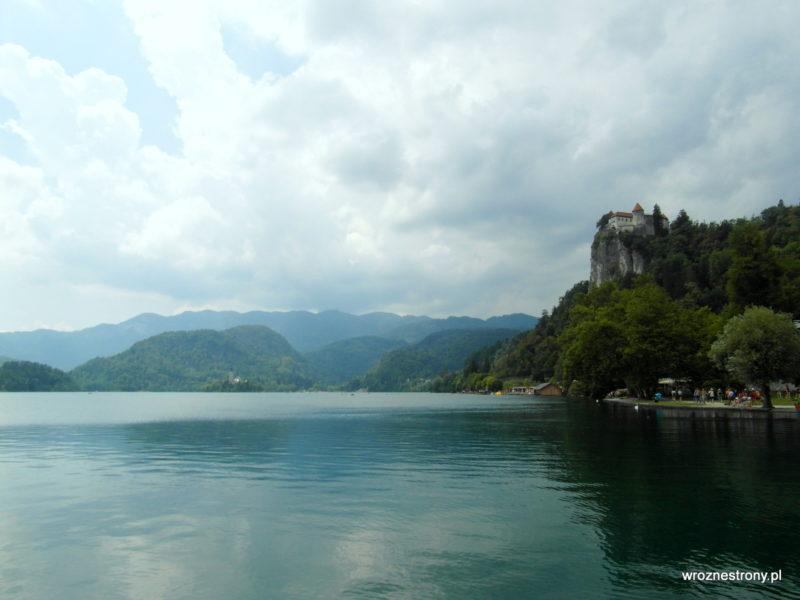 Jezioro Bled, w oddali widać wyspę i dużo szarych chmur